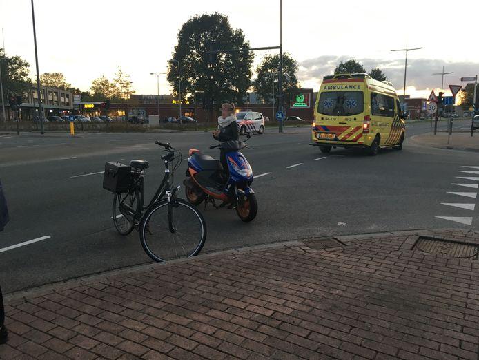 De bestuurster van de scooter kijkt hoe hulpverleners zich over de fietser ontfermen.