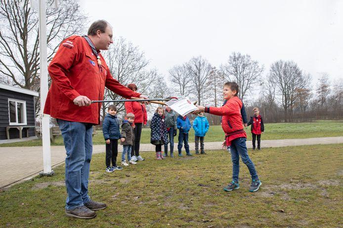 Voorzitter Huub van de Zande overhandigt 'coronaproof' een oorkonde aan het 100ste lid van de scouting in Zierikzee Matthias Verkamman