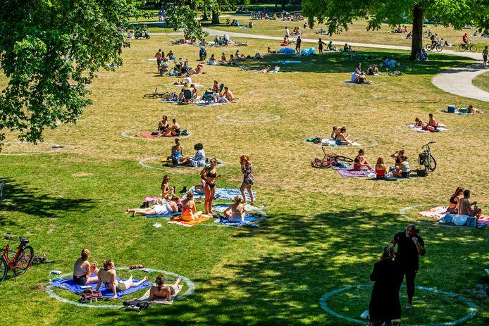 Mensen houden zich keurig aan de nieuwe cirkels die op het gras zijn gezet.