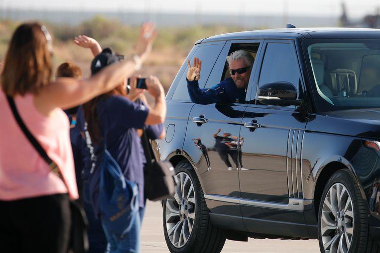 Branson zwaait naar toeschouwers voor de vlucht.  Beeld REUTERS