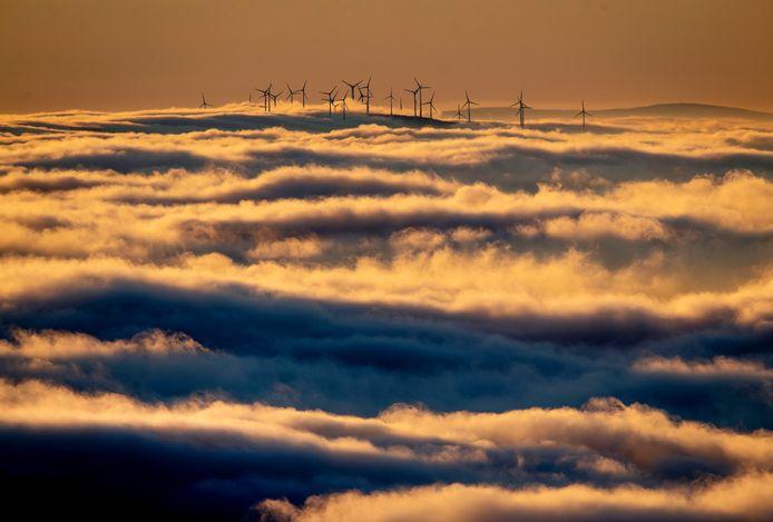 Sur cette photo d'archive du 6 janvier 2020, des éoliennes se dressent sur une colline et sont entourées de brouillard et de nuages dans la région du Taunus, près de Francfort, en Allemagne.