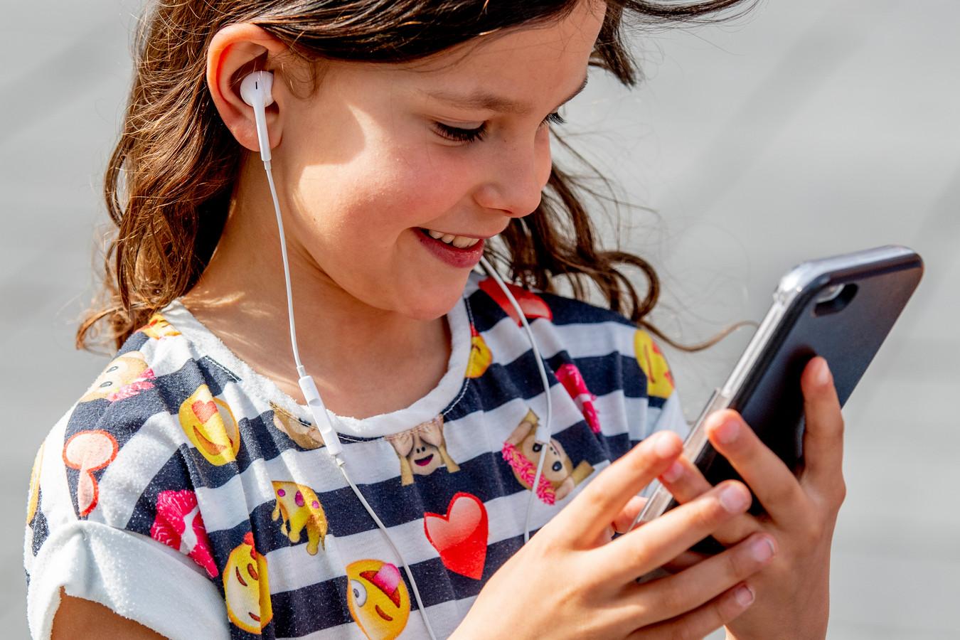 Een meisje van 7 met haar iPhone. De leeftijd waarop kinderen een mobiele telefoon krijgen, daalt gestaag.