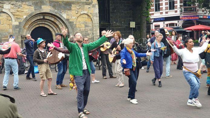 Een groep van zo'n dertig mensen, waaronder musici, zorgden zaterdagmiddag voor een verrassing op een volle Oude Markt in Enschede.