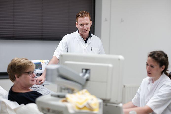 Nicole te Kortschot (links) ligt op de behandeltafel in de nieuwe vaatpoli van het Slingeland Ziekenhuis in Groenlo en wordt onderzocht door laborant Jet Grotenhuis (rechts) en vaatchirurg Gert-Jan Lauret