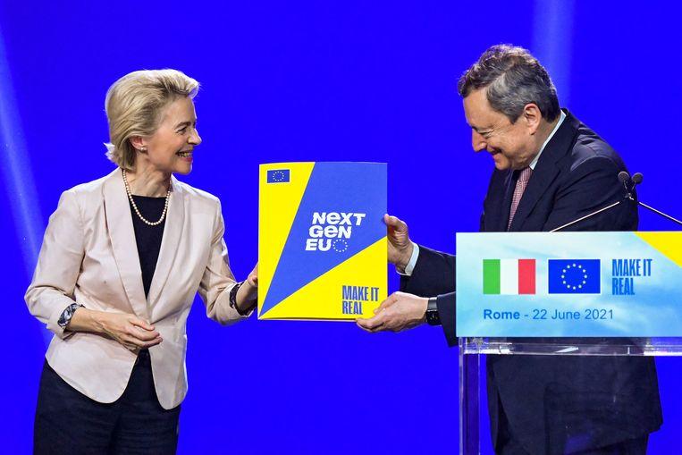 Von der Leyen (Europese Commissie) overhandigt de Italiaanse premier Draghi dinsdag symbolisch het Europese herstelplan, tijdens een gezamenlijke persconferentie in Rome. Beeld AFP