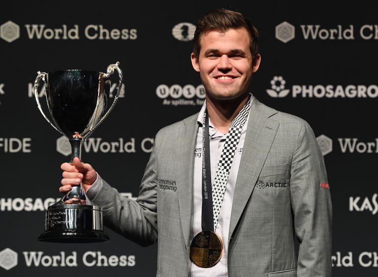 Winnaar van de tweekamp, Magnus Carlsen, poseert met zijn trofee.  Beeld EPA