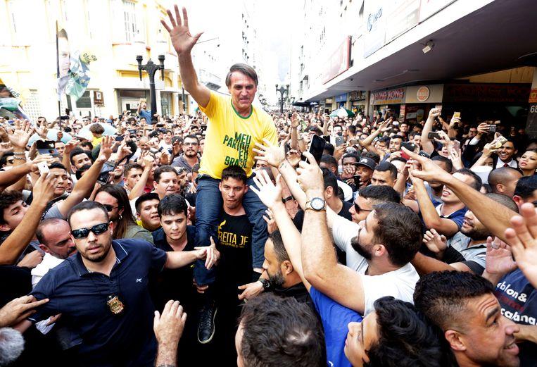 De Braziliaanse presidentskandidaat Jair Bolsonaro gaat op de schouders bij zijn aanhang in Juiz de Fora. Kort daarop zal hij worden neergestoken. Beeld AP