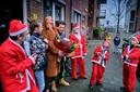 Annemieke Ooyen (midden links) en haar gezin zijn ontzettend blij met de komst van de vier kerstmannen. Ze kregen een pakketje met 21 sokken en een mooie grote bos bloemen.
