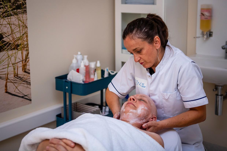 Borstkankerpatiënte Berlinda Van Maerrem (52) krijgt een massage en gelaatsverzorging van An Rogiers. Beeld Photonews