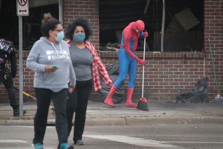 Verkleed als Spider-Man veegt iemand de stoep na een avond van rellen in Minneapolis, enkele dagen na de dood van George Floyd.  Beeld Scott Olson / AFP