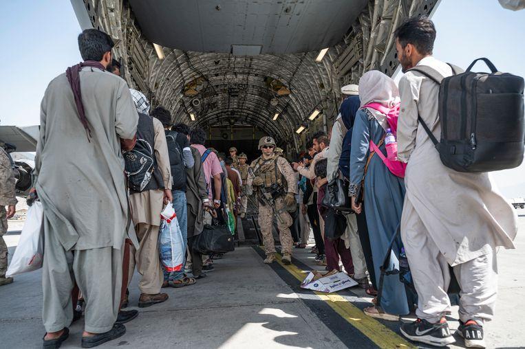 Amerikaanse militairen begeleiden Afghaanse evacués die aan boord gaan van een transportvliegtuig op de luchthaven van Kaboel. Beeld AP
