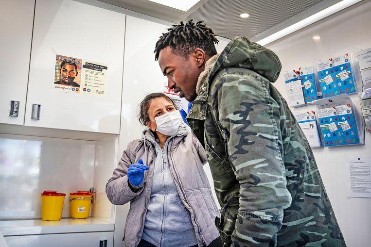 Dina Khosbin van Dokters van de Wereld controleert een man uit Tsjaad. Beeld Guus Dubbelman / de Volkskrant