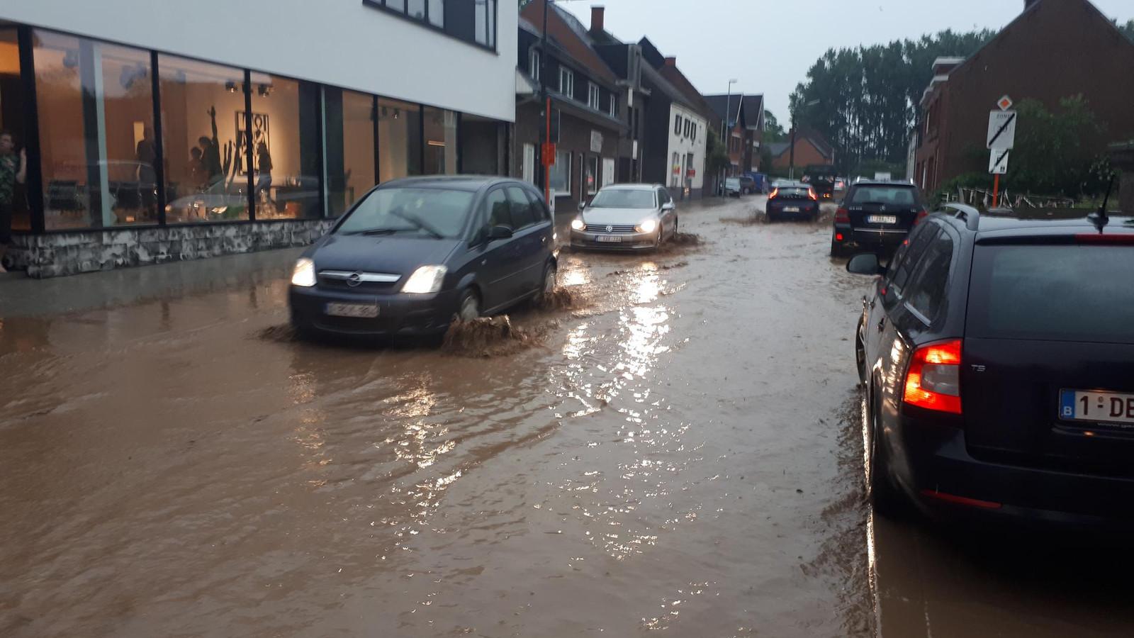 Automobilisten banen zich een weg door de Polbroek, die in een kleine rivier veranderd is.