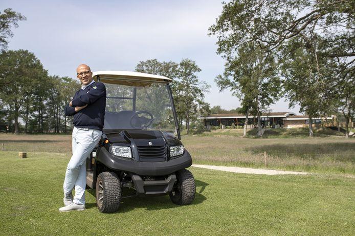 Frank Agterbos, eigenaar van Weleveld Golf, op golfterrein met horeca gedeelte op de achtergrond