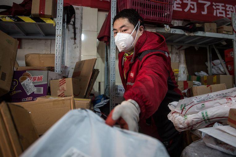 Een postbode sorteert pakketjes in een postkantoor in Wuhan.