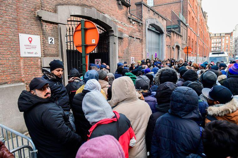 Mensen wachten in de rij bij de Dienst Vreemdelingenzaken. Beeld BELGA