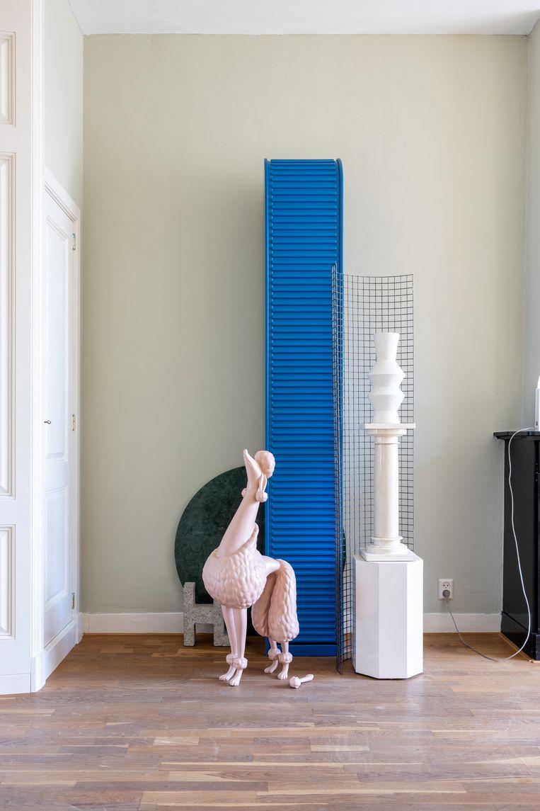 In elk hoekje valt wel iets te zien: van kleine stillevens opgebouwd uit de Tahiti-lamp van Ettore Sottsass, een spiegel uit de kringloopwinkel en een vaas van Studio Truly Truly of een blauwe roldeurkast van Pastoe met een beeld van een poedel tot grote composities waar onder meer stoelen op kasten worden gezet.  Beeld Henny van Belkom