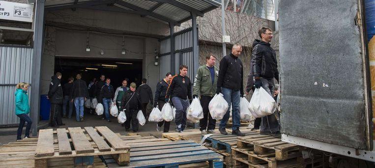 Vrijwilligers laden voedselpakketten in vrachtwagens bij het voetbalstadion van Sjachtar Donetsk Beeld RV