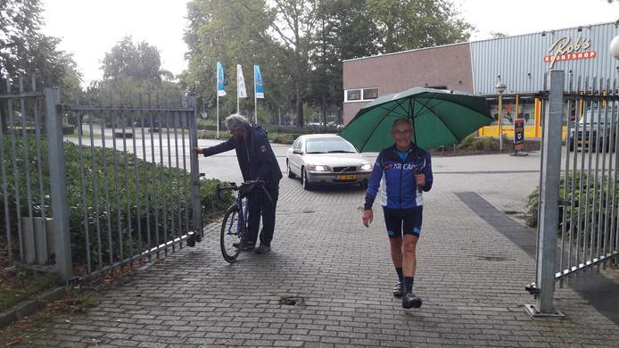 De wielerheld uit Warnsveld arriveert in de stromende regen bij de Geleense wielerbaan. Een medewerker van de wielerbaan heeft Theo's fiets bij de hand.