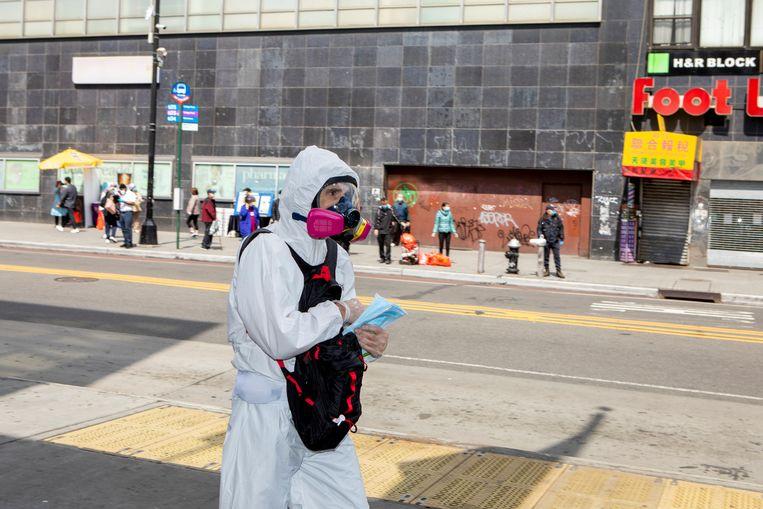 Meneer die maskers en handschoenen uitdeelt in Main street, de hoofdstraat van Chinatown in Flushing Queens. Beeld Chantal Heijnen