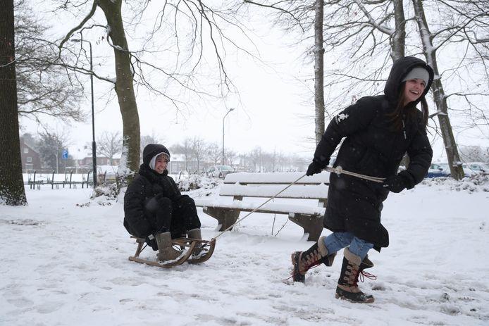 De vriendinnen Noor (op de slee) en Marloes ploegen zich door de sneeuw in Helmond