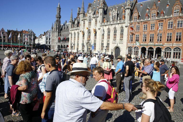 Mensen op de Grote Markt in Brugge. Beeld BELGA
