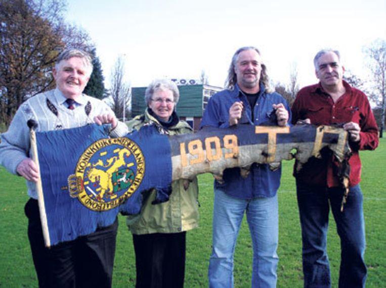 Vlnr: Toon Molenaar, Nel Molenaar, Gerard van Schijndel en Bas Mol tonen de vlag die uit de puinhopen kwam. Foto: Edwin Schoon. Beeld