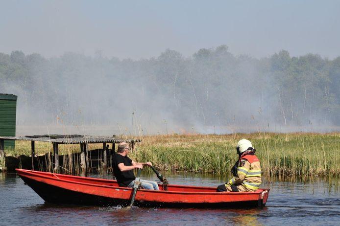 De brandweer moet per boot naar de natuurbrand toe.
