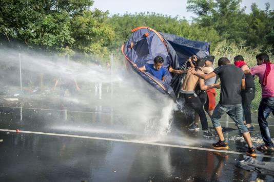De Hongaarse politie gebruikt waterkanonnen om vluchtelingen te verjagen bij de grens.