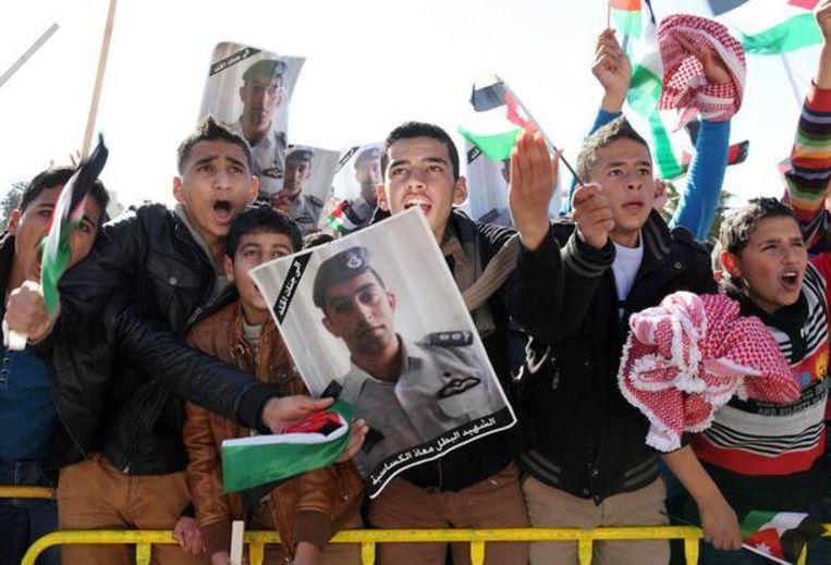 Demonstranten met foto's van de vermoorde Jordaanse piloot.