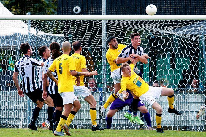 Hercules-verdediger Bjorn van Gorkom (rechts) kopt de bal weg tussen twee spelers van UNA in.