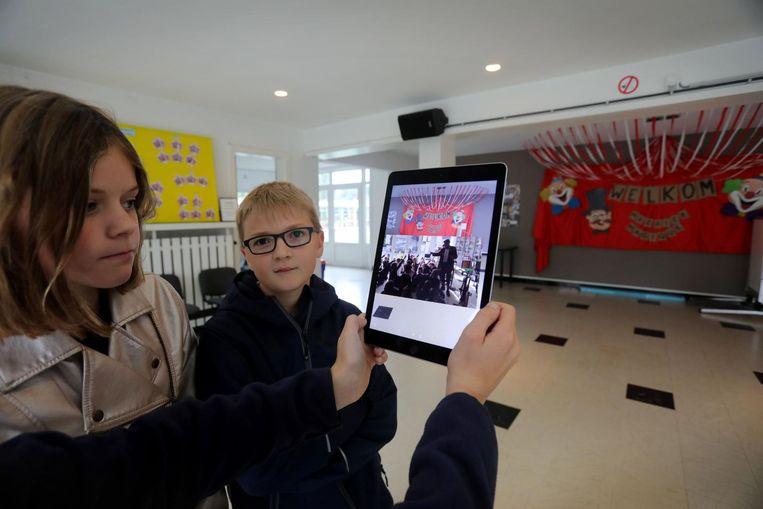 In de grote zaal verschijnt een filmpje van een samenkomst van de leerlingen.