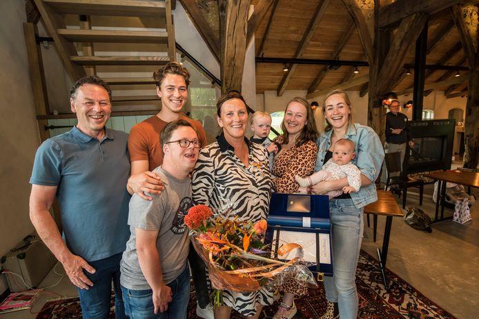 Bernadet Wieffer als stralend middelpunt van haar gezin. Echtgenoot Rob (links) speldde haar de koninklijke onderscheiding op.