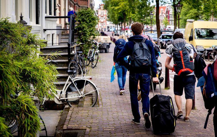 Toeristen met rolkoffers in Amsterdam Beeld anp