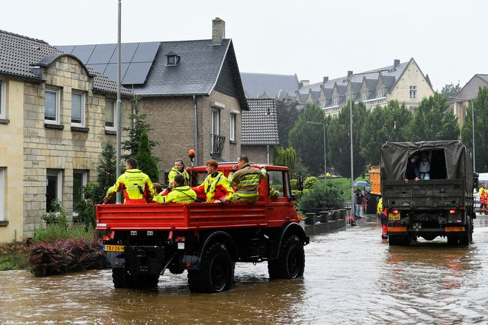 Reddingswerkers en militairen helpen in Valkenburg mensen uit hun huizen.