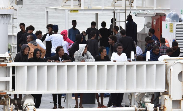 Migranten op het schip in Catania. Beeld EPA
