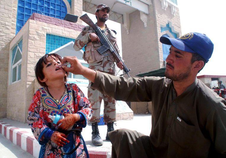 Een gezondheidswerker vaccineert een meisje tegen polio bij de Afghaans-Pakistaanse grens Beeld epa
