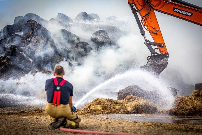 Bij een brand in een grote berg hooibalen in Goudswaard is de brandweer langdurig bezig met blussen. De brand gaat gepaard met veel rook, die in de omgeving te zien is.