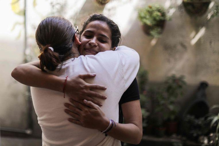 De Belgisch-Nicaraguaanse Amaya Coppens knuffelt een vriendin na haar vrijlating begin deze week.  Beeld AFP