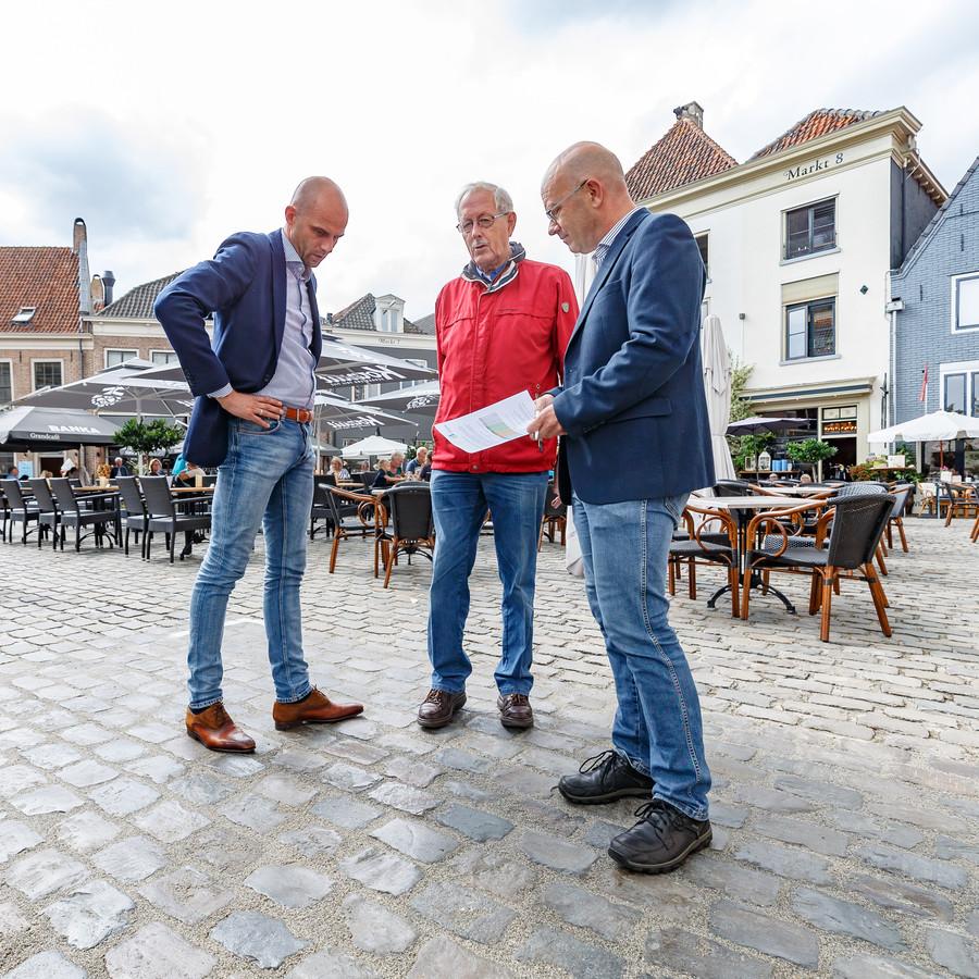Wethouder Auke Schipper (links) met Roel Brand en projectleider Ronald IJsselsteijn bij een testvlak op de Markt in Hattem.