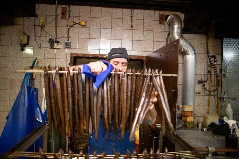 In alle vroegte hangt Jan Aart van Triest zijn paling op in de ambachtelijke rokerij in Elburg. Binnenkort is dat verleden tijd. Beeld Herman Engbers