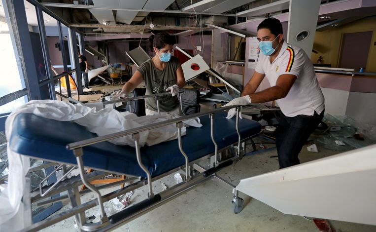 Ook de ziekenhuizen zelf zijn vernield. Twee Libanezen zoeken tussen het puin naar bruikbaar materiaal. Beeld REUTERS