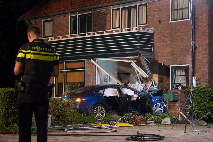 De gevel van de woning in Bilthoven is flink beschadigd nadat de elektrische auto half naar binnen reed.