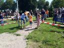 Luke en Linde verrichten onder toeziend oog van wethouder Klomberg de officiële opening van de natuurspeelplaats in de Dierense Speeltuin. Ze hebben alledrie hun schoenen al uit, om het waterpad op te gaan.