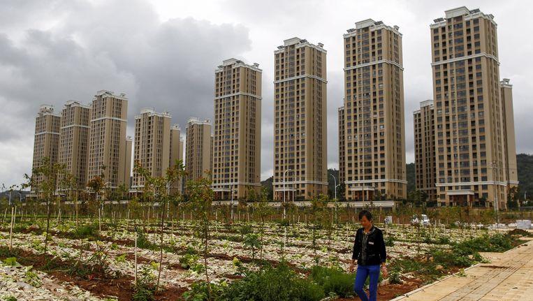 Een Chinese boer bij pasgebouwde woontorens in het nieuwe district Kunming in de provincie Yunnan. Beeld REUTERS