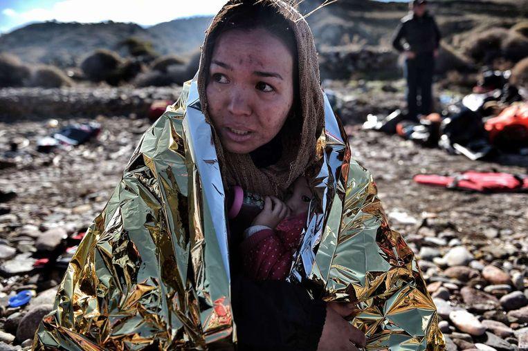 Vrouw met kind bij aankomst op Lesbos na de oversteek vanuit Turkije Beeld afp