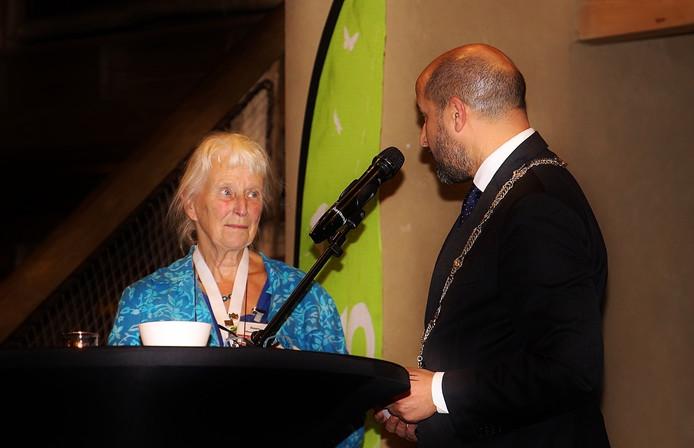 Suus Houtman krijgt een koninklijke onderscheiding van burgemeester Ahmed Marcouch.