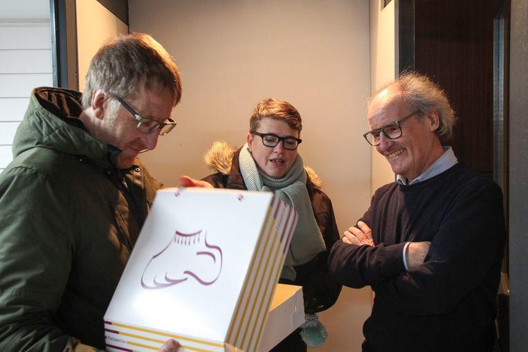 Filip Lombaert en Veerle Renier van Groen overhandigen een van de Budd'Iz-vrijwilligers een 'Izegems schoentje, een lokale lekkernij als bedankje.