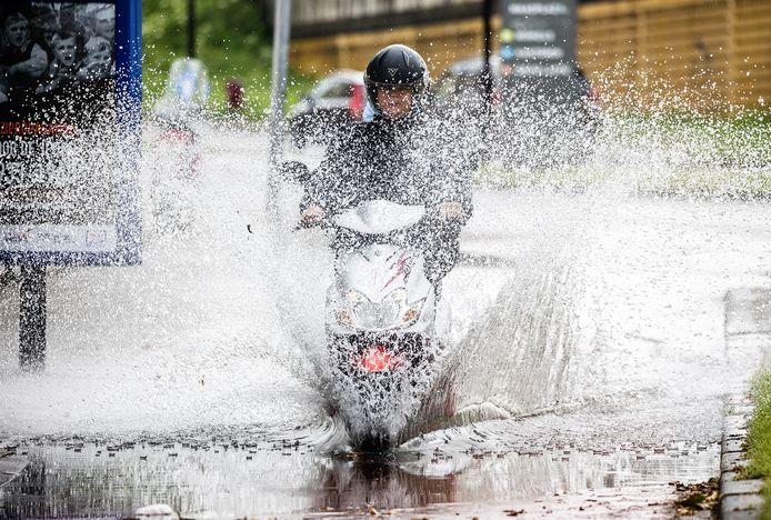 Fietsers en scooters rijden over een met water ondergelopen fietspad in Dordrecht, langs de Korte Parallelweg.