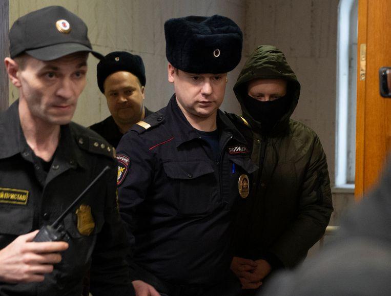 Een van de Russische politieagenten die de bekende onderzoeksjournalist Ivan Goloenov in een val wilden laten lopen, wordt weggeleid uit een rechtszaal in Moskou. De agenten arresteerden Goloenov nadat zij zelf drugs bij hem hadden verstopt. Beeld AP